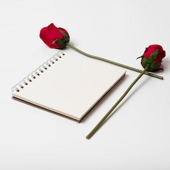 Leerer notizblock mit rosen auf tabelle