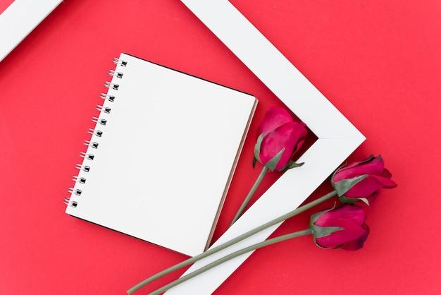 Leerer notizblock mit roten rosen im rahmen
