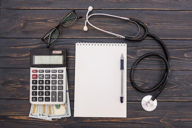 Leerer notizblock mit stift, stethoskop, taschenrechner, dollar auf einer holzoberfläche