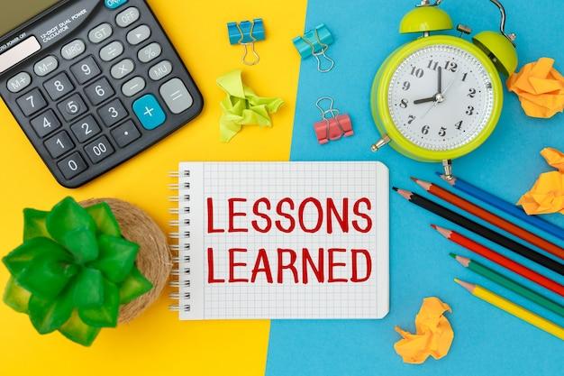 Leerer notizblock mit text lektionen lernen mit schulbürobedarf