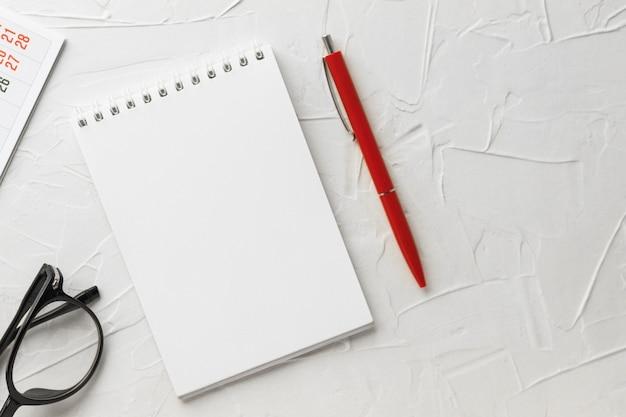 Leerer notizblock, stift, brille und kalender auf weißem kittbeschaffenheitshintergrund. notizbuch für notizen und ideen. geschäftskonzept