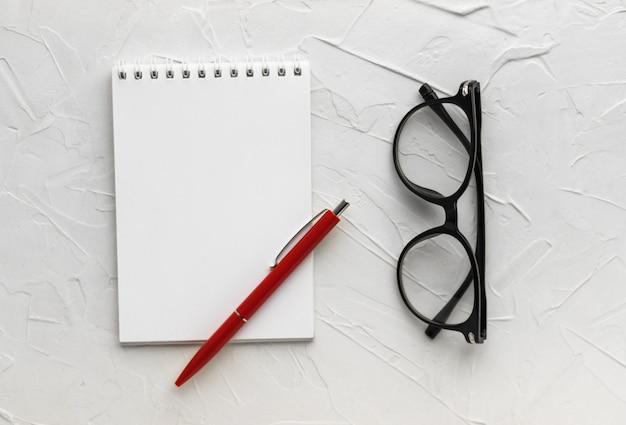Leerer notizblock, stift und brille auf weißem kittbeschaffenheitshintergrund. geschäftskonzept. notizbuch für notizen und ideen