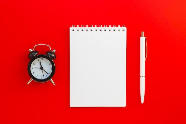 Leerer notizblock, stift und mini-wecker auf rotem hintergrund. zeiteinteilung. notizbuch für ideen, nachrichten, listen und inspirationen.