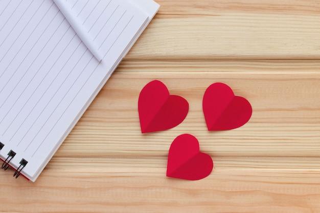 Leerer notizblock, stift und rote herzen auf holztisch. liebesnachricht. natürliche oberfläche. valentinstag thema. flache lage, draufsicht, kopierraum.