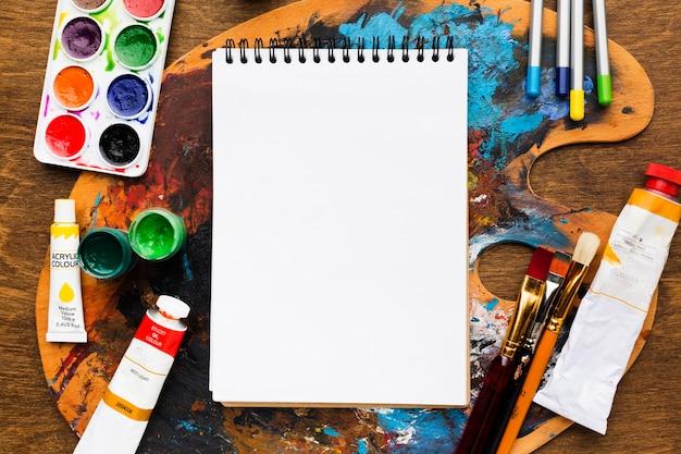 Leerer notizblock über schmutziger farbpalette