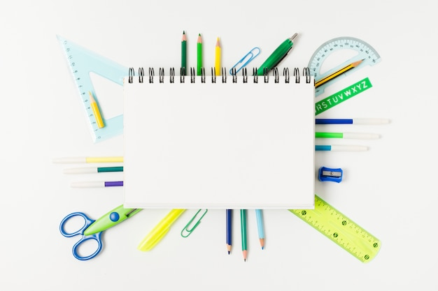 Leerer notizblock umgeben durch schreibtischversorgungen