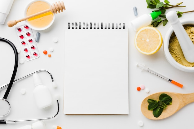Leerer notizblock umgeben von natürlichen und medizinischen behandlungen