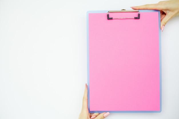 Leerer ordner mit rosa papier. übergeben sie das halten des ordners und des griffs auf weißem hintergrund. exemplar.