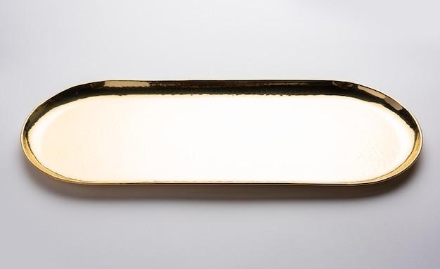 Leerer ovaler oder runder thali oder teller aus messing, ppital oder gold auf weißer oberfläche