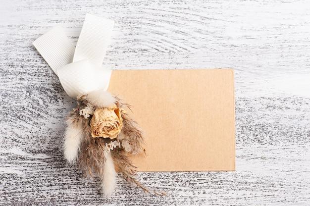 Leerer papier- und kraftumschlag mit neutralem blumenstrauß aus trockenen blumen. hochzeitsmodell auf weißem tisch