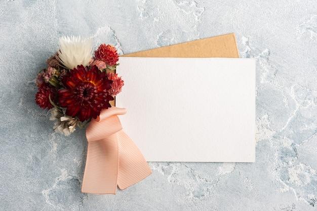 Leerer papier- und kraftumschlag mit rotem blumenstrauß. hochzeitsmodell auf grauem tisch