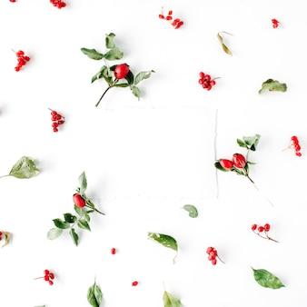 Leerer papierrohling und minimales kreatives beerenanordnungsmuster auf weiß.