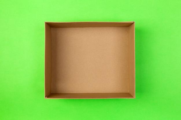 Leerer papppapierkasten auf grün. lieferkonzept, ansicht von oben