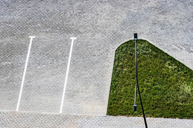 Leerer parkplatz im hof eines hauses mit weißen markierungen auf pflastersteinen oder pflasterplatten. sicht von oben. städtische umgebung.