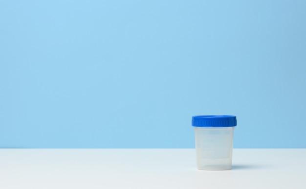 Leerer plastikbehälter für die sammlung von analysen auf einem weißen tisch, blauer hintergrund, kopienraum