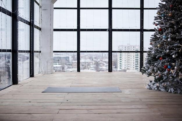 Leerer platz im fitnesscenter mit großen fenstern und naturholzboden. abgerollte yogamatte auf dem boden, keine menschen. verzierter weihnachtsbaum im dachboden.