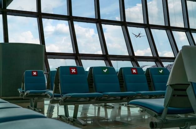 Leerer platz in der abflughalle am flughafenterminal. abstand für einen sitz halten abstand, um das coronavirus und die soziale distanzierung der passagiere aus sicherheitsgründen zu schützen. gesehenes flugzeug fliegt durch glasfenster.