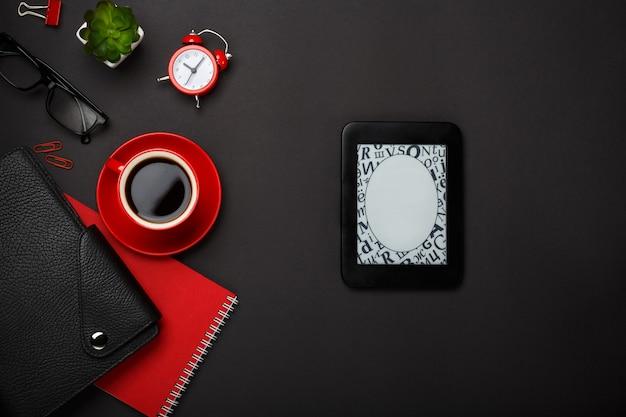 Leerer platzdesktop der schwarzen kaffeetasse-notizblockwecker-blumentagebuchgläser des hintergrundes roten
