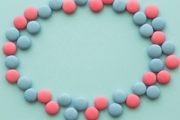 Leerer rahmen gemacht mit den runden rosa und blauen süßigkeiten auf farbigem hintergrund