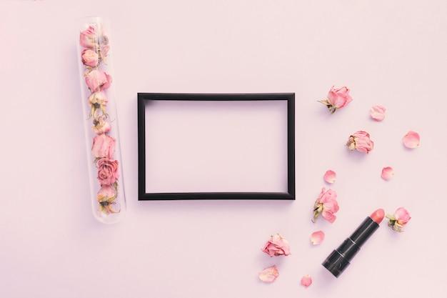 Leerer rahmen mit den rosafarbenen blumenblättern und dem lippenstift auf tabelle