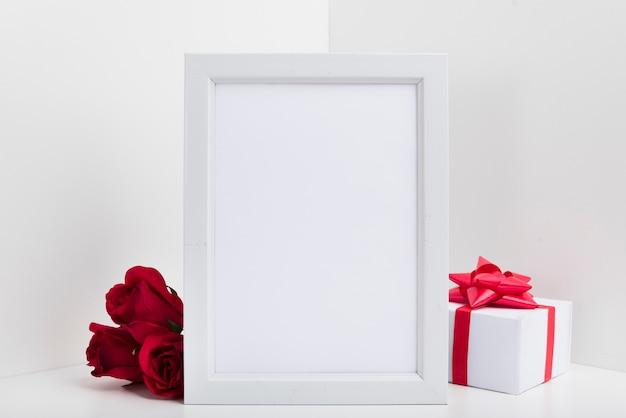 Leerer rahmen mit geschenkbox und roten rosen