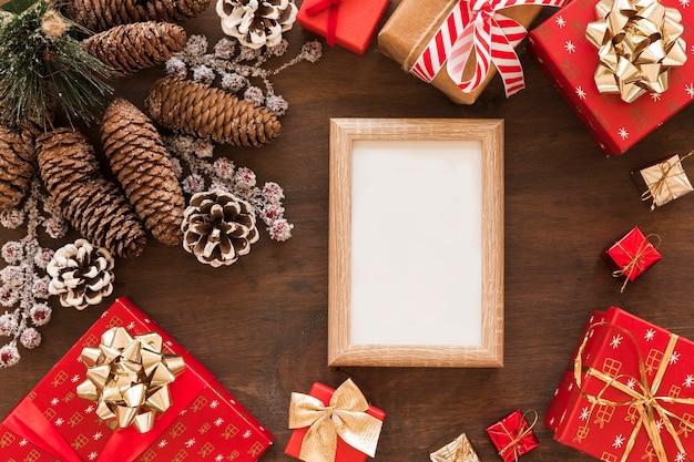 Leerer rahmen mit geschenkboxen und zapfen