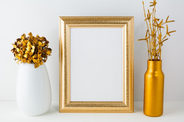 Leerer rahmen mit goldener vase