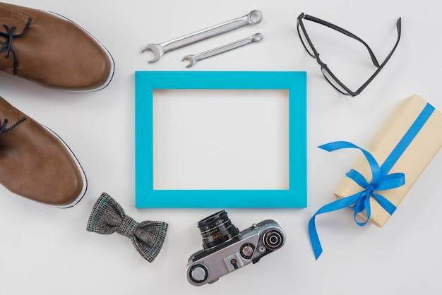 Leerer rahmen mit kamera, mannschuhen und geschenk