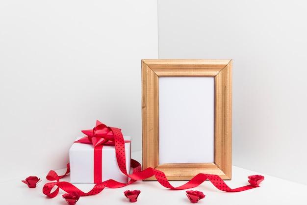 Leerer rahmen mit kleiner geschenkbox und rosen