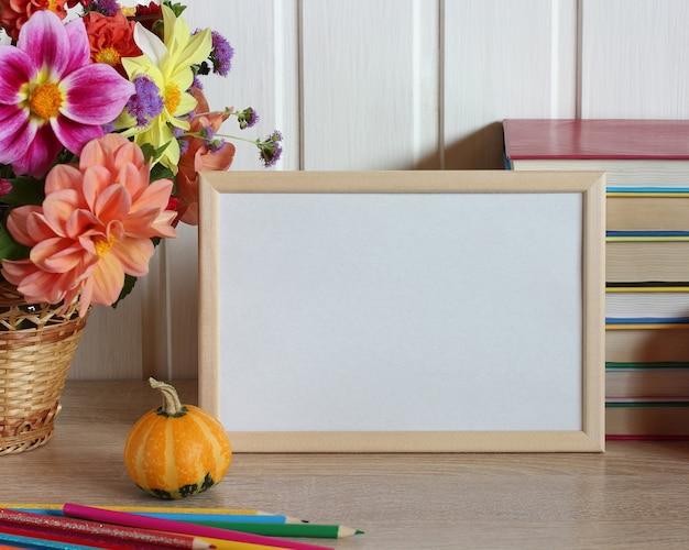 Leerer rahmen mit weißem hintergrund auf dem schreibtisch mit lehrbüchern, dahlien und buntstiften zurück zum tag des lehrers für den schulkopierraum Premium Fotos