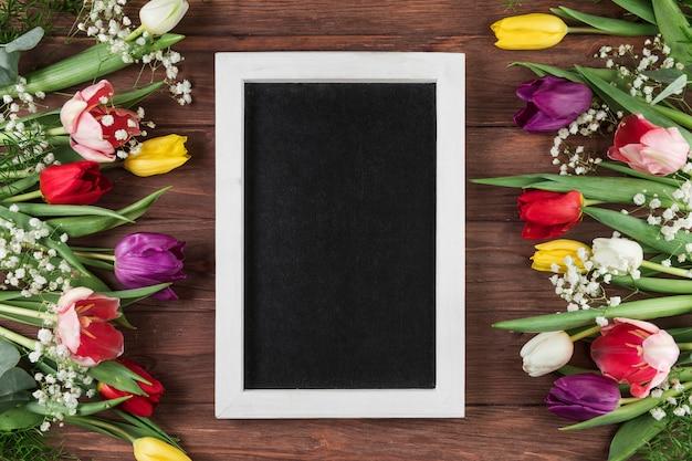 Leerer rahmen mit weißer grenze zwischen den bunten tulpen und der atemblume des babys auf hölzernem schreibtisch