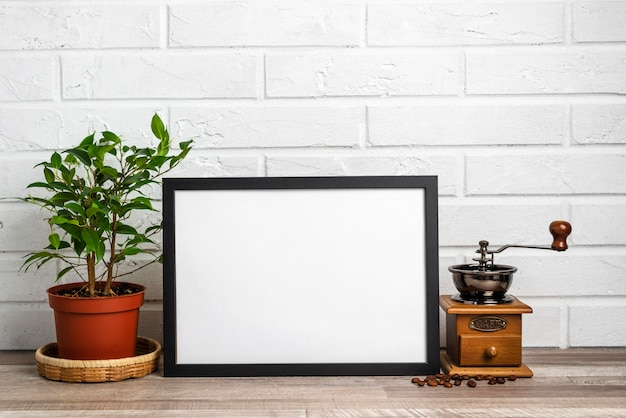 Leerer rahmen neben blumentopf und mühle Kostenlose Fotos