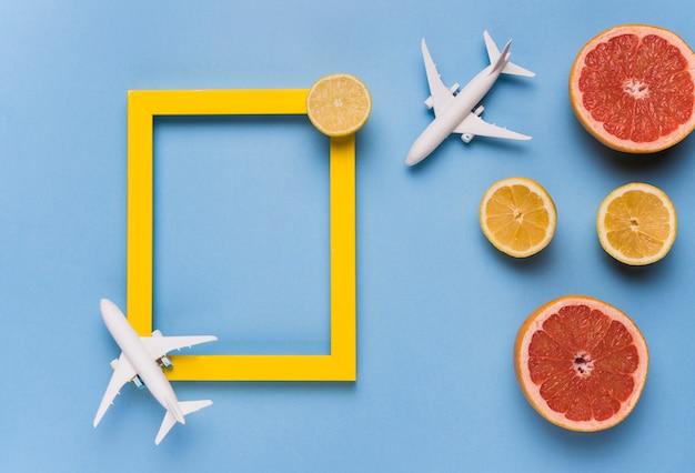 Leerer rahmen, spielzeugflugzeuge und frucht