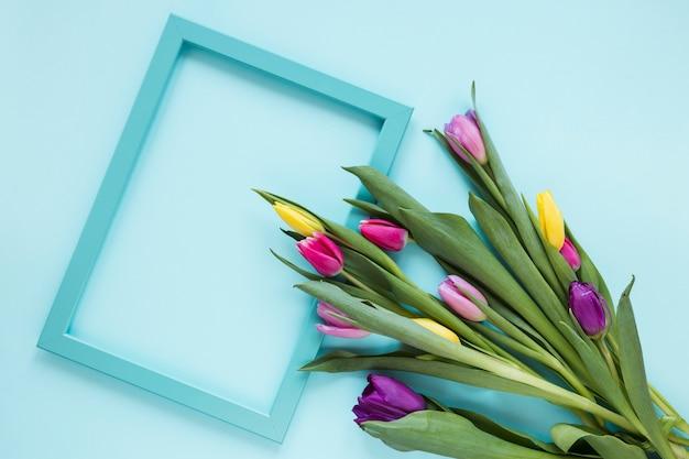 Leerer rahmen und blumenstrauß von bunten tulpenblumen