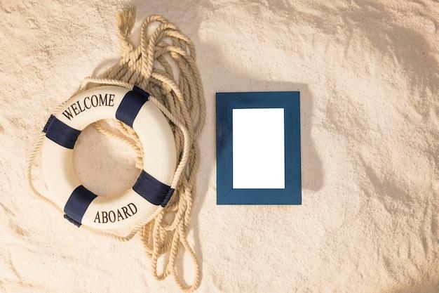 Leerer rahmen und marinerettungsring auf sand
