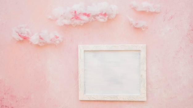Leerer rahmen und wolken auf dem rosa gemasert