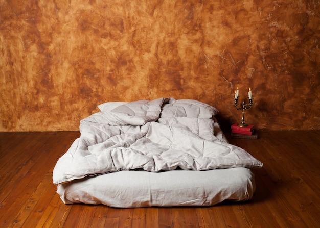 Leerer raum im dachboden mit einer matratze als bett