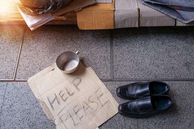 Leerer raum im obdachlosenheim auf der straße in der modernen stadt, jemand gab obdachlosen schuhe