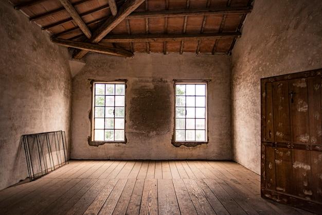 Leerer raum in einem verlassenen haus mit fenster und holzboden