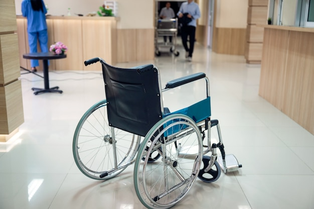 Leerer rollstuhl geparkt auf korridor im krankenhaus