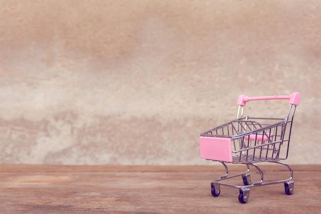 Leerer rosa einkaufswagen auf braunem holztisch.