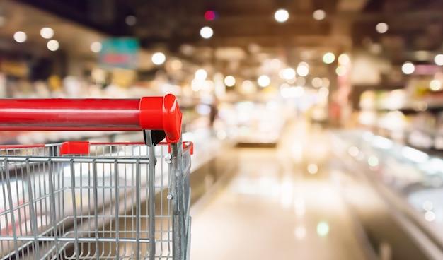 Leerer roter einkaufswagen mit abstrakter unschärfe-supermarkt-discountergang und produktregalinnenraum defokussierten hintergrund