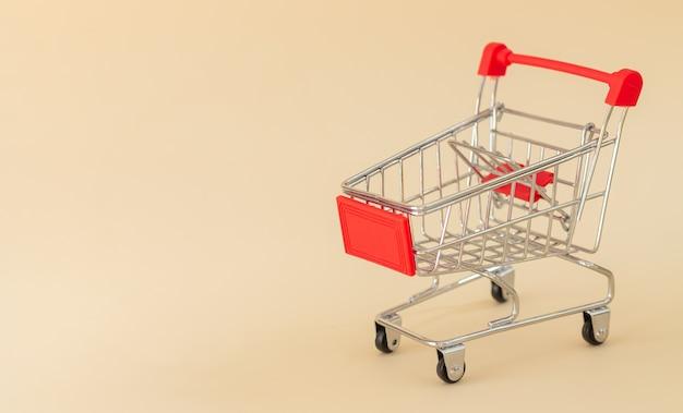 Leerer roter einkaufswagen oder wagen auf beigem hintergrund mit kopienraum