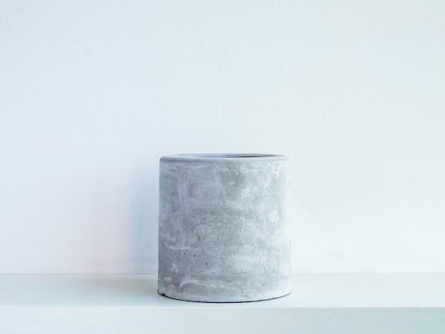 Leerer runder betonblumentopf auf einem weißen hölzernen regal lokalisiert auf weißer wand. kleiner diy-zementübertopf für kakteen, sukkulenten oder blumen.