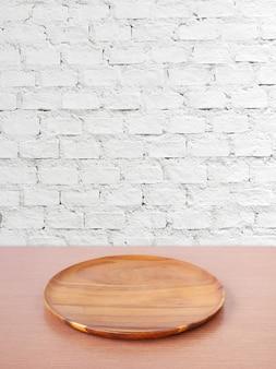 Leerer runder hölzerner behälter auf tabelle über weißem backsteinmauerhintergrund