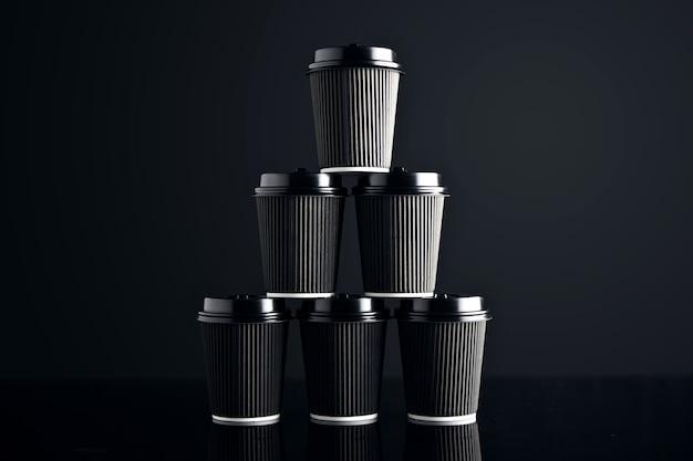 Leerer satz schwarzer pappbecher zum mitnehmen, geschlossen mit pyramidenförmigen kappen auf schwarz und verspiegelt. einzelhandelspräsentation