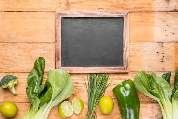 Leerer schiefer mit reihe von bokchoy; brokkoli; zitrone; paprika; schnittlauch auf schreibtisch aus holz