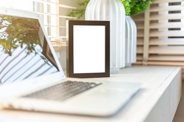 Leerer schwarzer arbeitsplatz des rahmens auf dem tischplattenarbeitsplatz mit laptop und blume