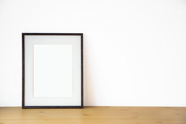 Leerer schwarzer bilderrahmen auf der weißen wand und dem bretterboden, innenhintergrund des fotos 3d des schablonenplakats