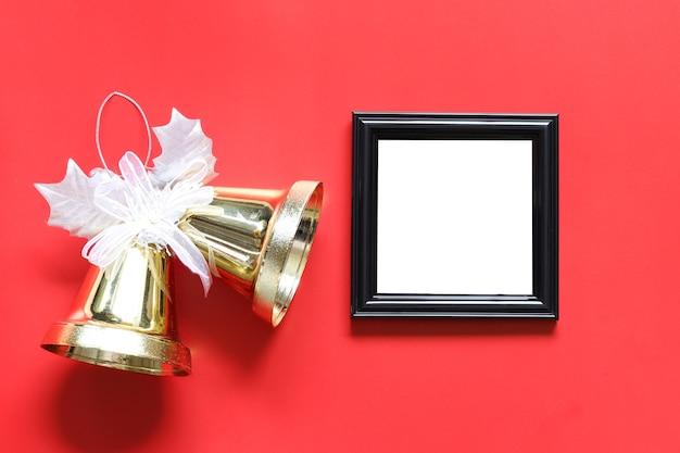 Leerer schwarzer fotorahmen und goldene glocke auf rotem hintergrund.